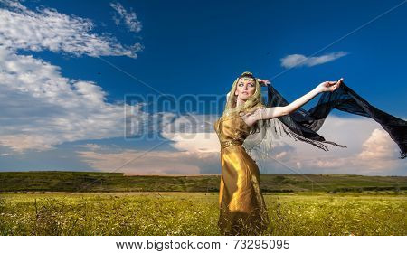 Lovely young lady posing dramatically with long black veil on green field. Blonde woman