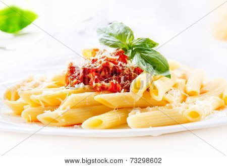 Pasta. Penne Pasta with Bolognese Sauce, Parmesan Cheese and Basil. Italian Cuisine. Mediterranean food