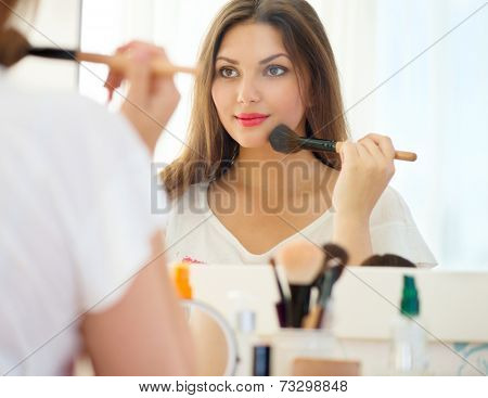 Beauty woman applying makeup. Beautiful girl looking in the mirror and applying cosmetic with a big brush. Girl gets blush on the cheekbones. Powder, rouge