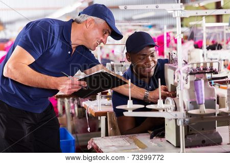 friendly textile factory foreman helping machinist with sewing machine