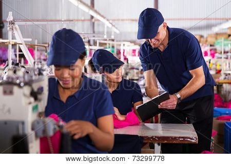 smiling clothing factory foreman explaining work to young machinist