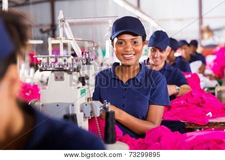 pretty african sewing machinist working in clothing factory