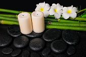 stock photo of frangipani  - spa concept of zen basalt stones three white flower frangipani candles and natural bamboo with dew closeup - JPG