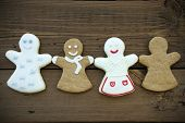 stock photo of ginger bread  - Four Different Happy Ginger Bread Woman on Wooden Background - JPG