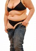 stock photo of flabby  - Overweight lady no longer able to fit into her pair of jeans - JPG