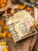 picture of indian currency  - Indian currency notes with a traditional lamp - JPG