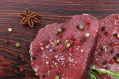 foto of peppercorns  - fresh raw beef fillet mignon on old retro style wood as background with rosemary peppercorn and salt - JPG