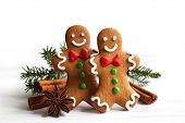 image of gingerbread man  - Smiling gingerbread men on white wooden background - JPG