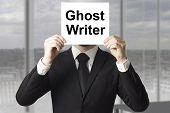 foto of incognito  - businessman in black suit hiding face behind sign ghost writer - JPG