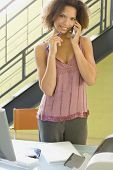 image of coy  - African businesswoman talking on telephone - JPG