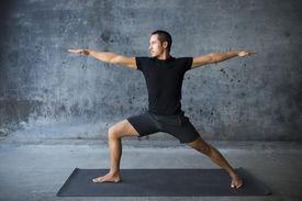 stock photo of yoga  - Man practicing yoga against a urban background - JPG