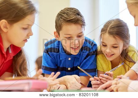 education, elementary school, learning and people concept - group of school kids with pens and papers writing in classroom