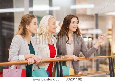 sale, consumerism and people concept - happy young women with shopping bags pointing finger in mall