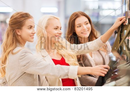 sale, consumerism and people concept - happy young women choosing clothes in mall