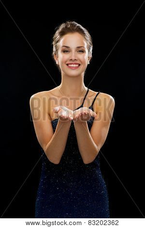 people, holidays, advertisement and luxury concept - smiling woman in evening dress holding something imaginary over black background