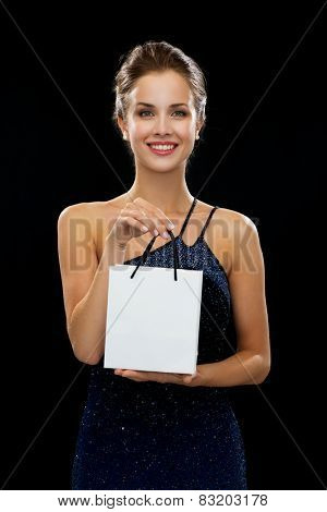 shopping, luxury, advertisement, holydays and sale concept - smiling woman with white blank shopping bag over black background