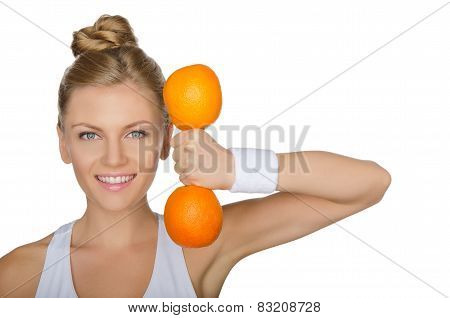 Beautiful Young Woman With Dumbbells Oranges