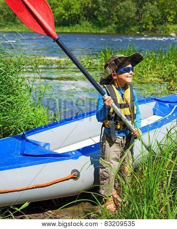 Boy near a kayak on the river