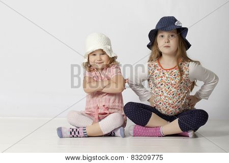 Two happy little sisters isolated on white