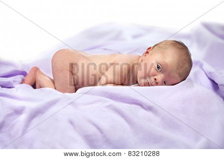 newborn baby lying down on white blanket body care maternity