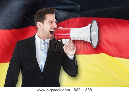 Young Businessman Shouting Through Megaphone
