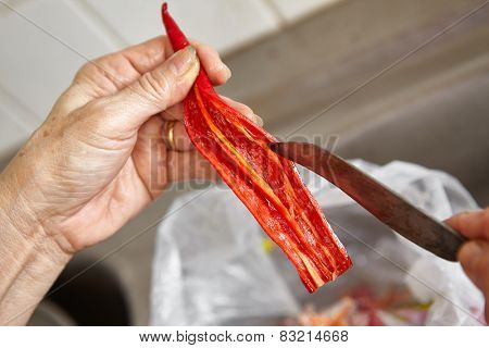 Hand cutting and cleaning chilli pepper form its seeds