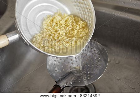 Draining the boiled instant noodle using sieve