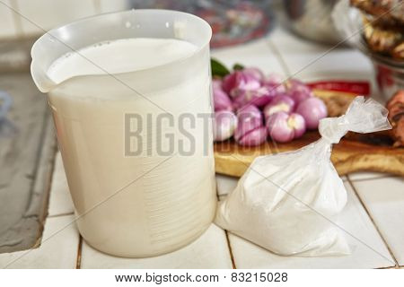Coconut milk on plastik glass as cooking ingredient