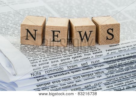 Wooden Blocks Spelling News On Newspapers