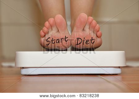 Feet on bathroom scale with hand drawn Start Diet text