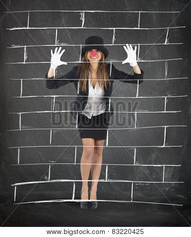 A funny girl mime imagining a wall