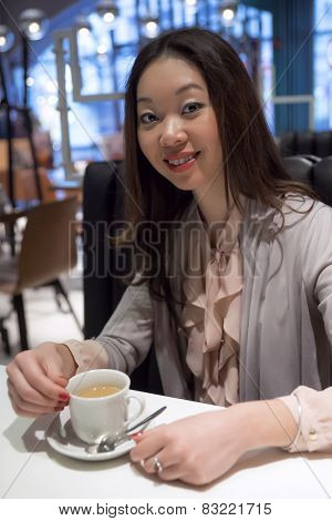 Affable beautiful Korean woman with a cup of coffee