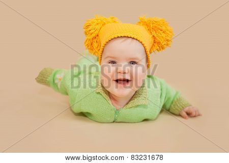 Smiling Baby In Knitted Suit And Hat