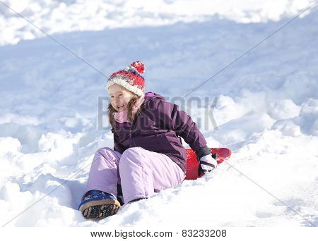 Young Girl Plays With Sledding On Snow In The Winter In The Mountains