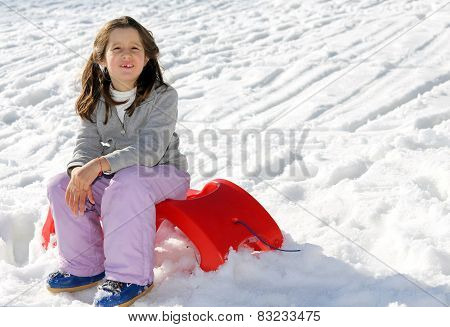 Pretty Girl Plays With The Red Sled On The Snow In The Winter