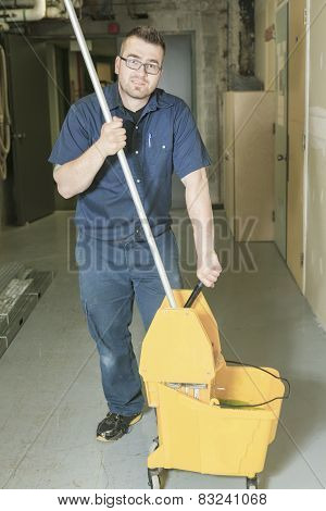 A serviceman who cleaning the floor with his mop