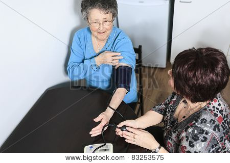 A girl help his mother taking her blood pressure