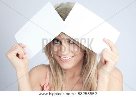 A Teenager girl hold white blank paper. Young smiling woman show
