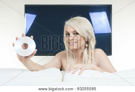 Woman in the living room show a CD-DVD