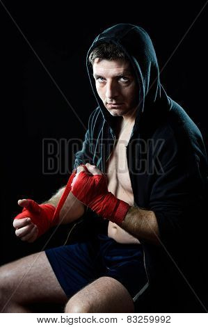 Man In Boxing Hoodie Jumper With Hood On Head Wrapping Hands Wrists Before Gym Training