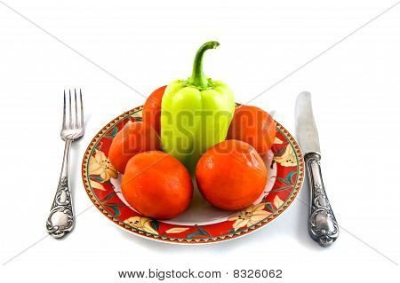 peppers and tomatoes on plate on white bacground