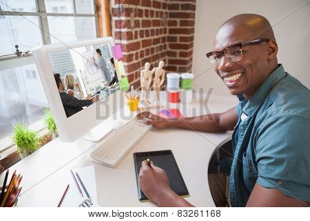 Business people in office at presentation against casual designer using graphics tablet