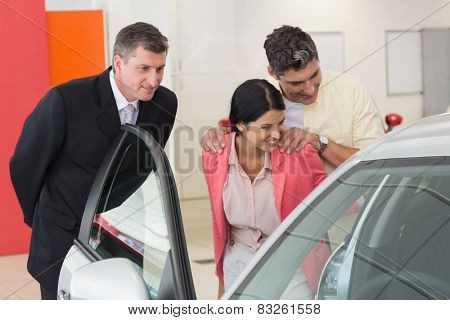 Car dealer showing the interior of a car to a couple at new car showroom