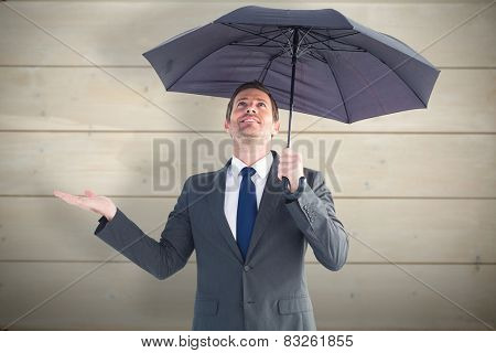 Businessman sheltering under black umbrella against bleached wooden planks background