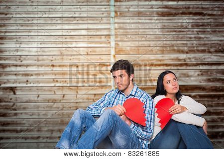 Young couple sitting on floor with broken heart against wooden planks