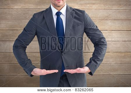 Businessman standing with hands out against wooden surface with planks