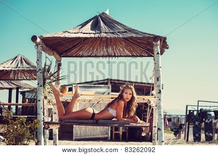 young woman in bikini  lie at shade at seaside beach enjoy in summer hot sunny day, full body shot
