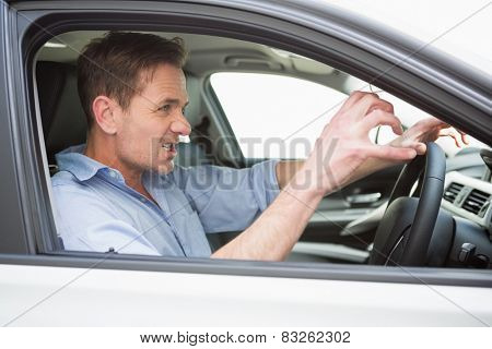 Handsome man experiencing road rage in his car