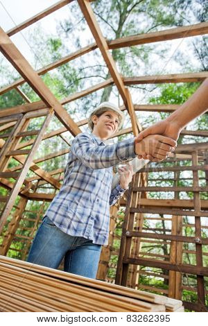 Low angle view of female architect shaking hand with male colleague at site
