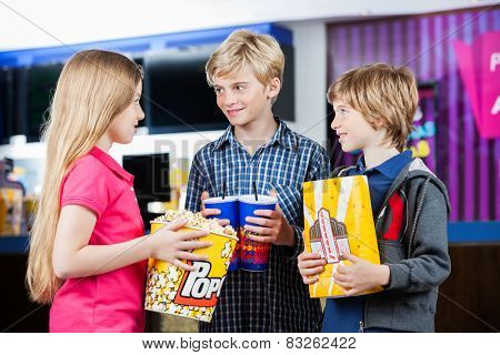 Happy siblings talking while holding popcorns and drinks at cinema